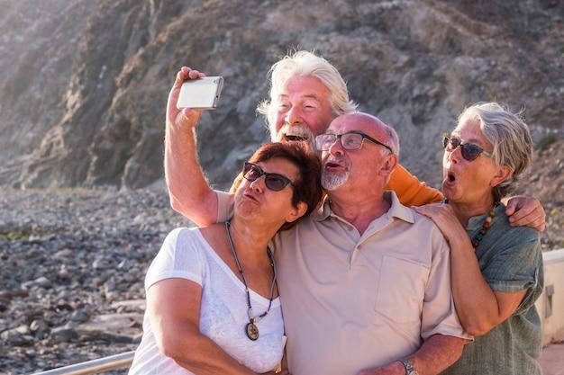 Czterech seniorów i dojrzałych ludzi razem na plaży lub w parku robi sobie selfie razem z wesołymi i zabawnymi twarzami, roześmianymi lub głupimi minami