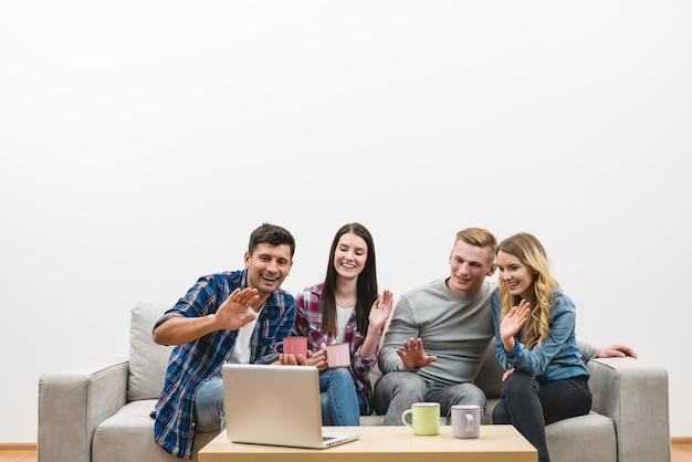 Czterech szczęśliwych ludzi gestykuluje w pobliżu laptopa na tle białej ściany