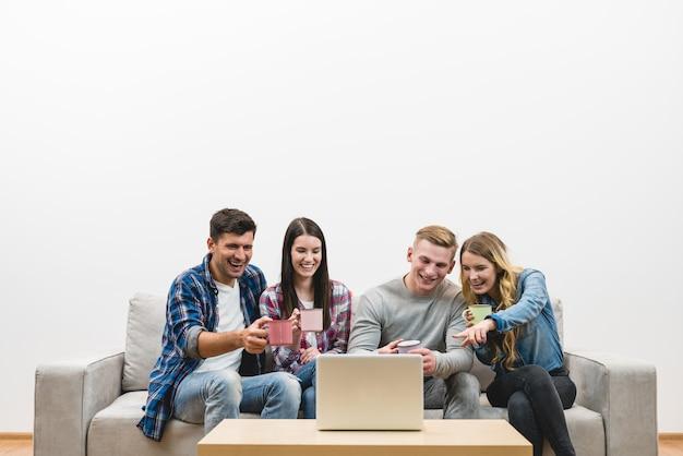 Czterech szczęśliwych ludzi z filiżankami siedzi obok laptopa na tle białej ściany