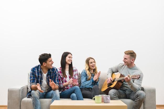 Czterech szczęśliwych ludzi z gitarą siedzi na kanapie na tle białej ściany