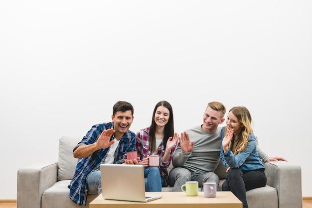 Czterech szczęśliwych przyjaciół gestykuluje w pobliżu laptopa na tle białej ściany