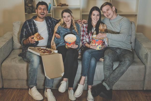 Czterech szczęśliwych przyjaciół z popcornem i pizzą ogląda film na kanapie