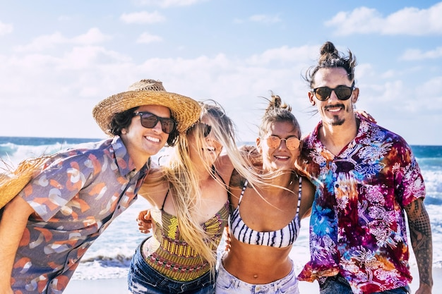 Czterech turystów młodych ludzi kaukaski chłopiec i dziewczęta modny wygląd i kolorowy styl życia uśmiech i cieszyć się letnimi wakacjami i wolnością na plaży z błękitnym niebem i oceanem