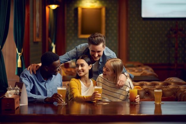 Czterech wesołych przyjaciół pije alkohol przy ladzie w barze. grupa ludzi odpoczywa w pubie, nocnym stylu życia, przyjaźni, uroczystościach