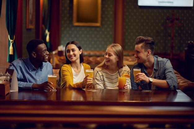Czterech wesołych przyjaciół pije alkohol przy ladzie w barze