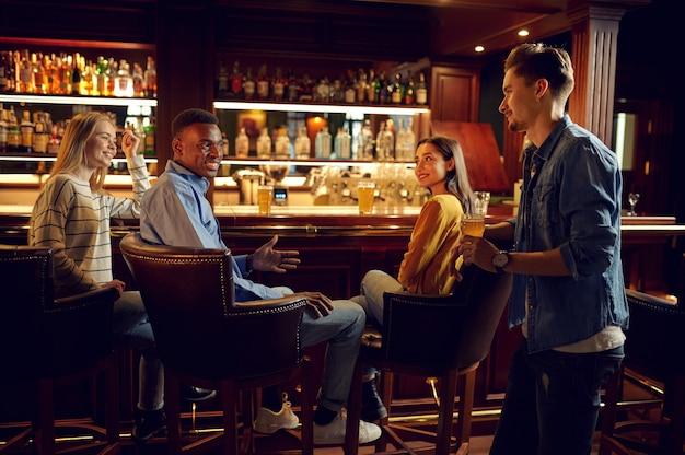Czterech wesołych przyjaciół pije piwo przy ladzie w barze