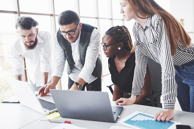 Czterech wielorasowych pracowników pracuje w biurze, korzystając z laptopa na stole