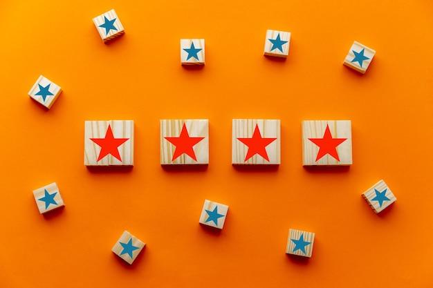Czterogwiazdkowy symbol na drewnianych kostkach na niebieskim tle. doświadczenie klienta, ankieta satysfakcji, ocena, podniesienie oceny i koncepcje najlepszych doskonałych usług oceny