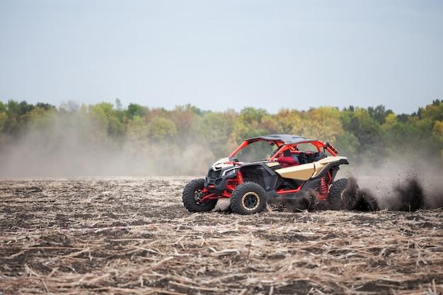 Czterokołowiec z kierowcą na zaoranym polu