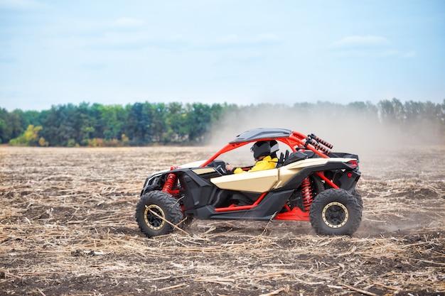 Czterokołowiec z kierowcą w kasku pędzi przez pole