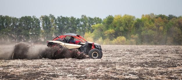 Czterokołowiec z mężczyzną za kierownicą pędzi przez pole