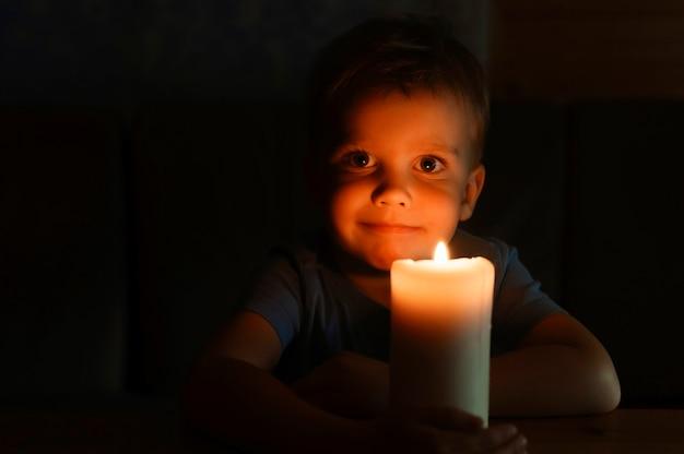 Czteroletni chłopiec podziwia płonącą świecę woskową wieczorem w domu