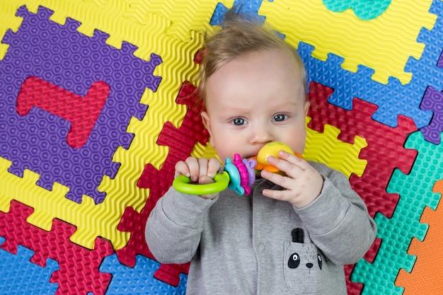 Czteromiesięczny chłopiec gryzie grzechotkę na jasnym, wielokolorowym dywanie