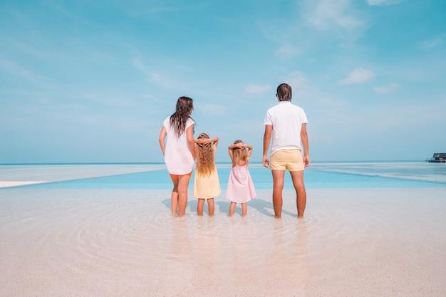 Czteroosobowa rodzina na wakacjach na plaży dobrze się bawi