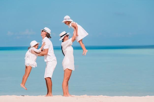 Czteroosobowa rodzina na wakacjach na plaży dobrze się bawić