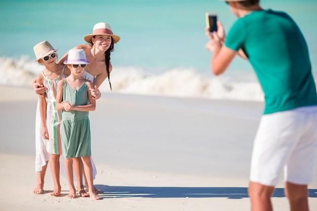 Czteroosobowa rodzina robi zdjęcie selfie na wakacjach na plaży.