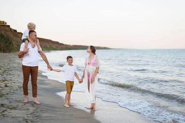 Czteroosobowa rodzina spacerująca brzegiem morza. rodzice i dwaj synowie. szczęśliwa przyjazna rodzina