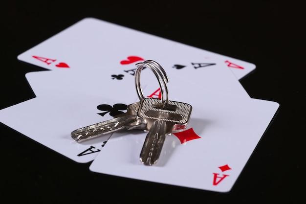 Cztery asy z kluczami od domu na czarnej powierzchni. wszystko jest zagrożone. hazard