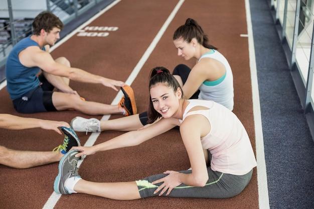 Cztery atletyczne kobiety i mężczyźni rozciągający się na bieżni