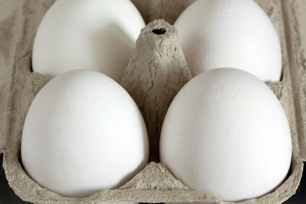 Cztery białe jajka umieszczone w jasnobrązowym kartoniku. zbliżenie.