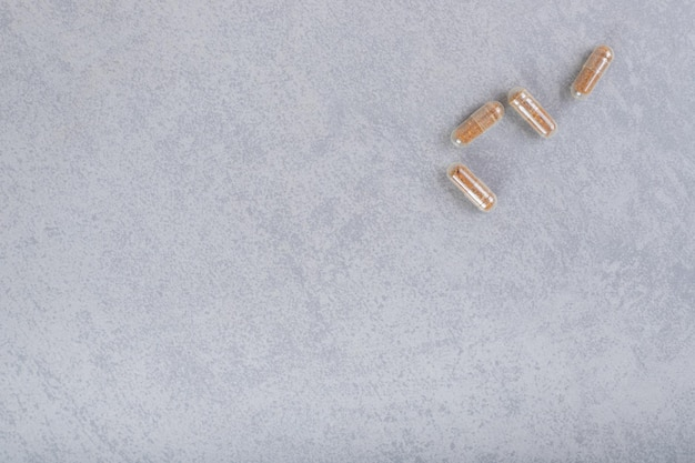 Cztery brązowe tabletki medyczne na szarym tle.