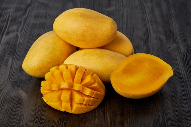 Cztery całe owoce mango na drewnianym stole i pokrojone w plasterki. duże soczyste jasne dojrzałe żółte owoce