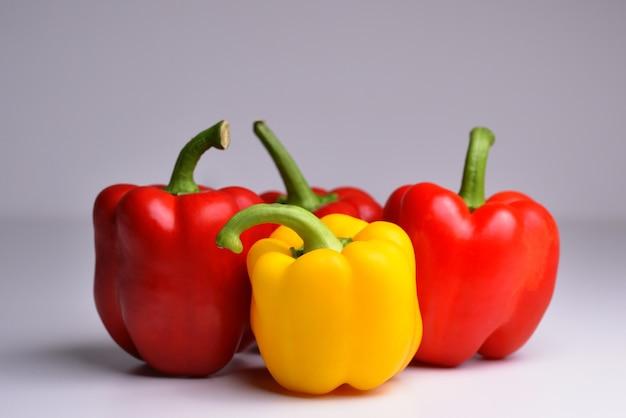 Cztery czerwone i żółte papryki na szarym tle ekologiczna zdrowa żywność