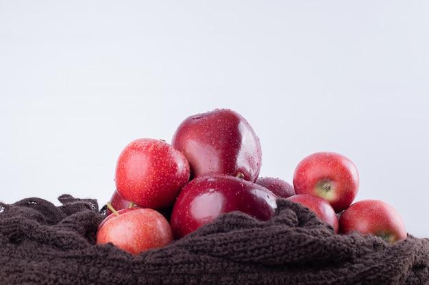 Cztery czerwone jabłko na brązowym płótnie.