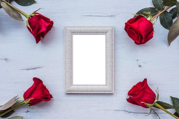Cztery czerwone róże na drewnianym stole, z ramką na zdjęcia, kopia przestrzeń