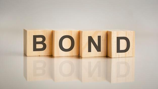 Cztery drewniane kostki z literami bond. koncepcja marketingu biznesowego. odbicie napisu na lustrzanej szarej powierzchni stołu