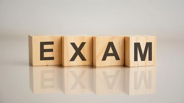 Cztery drewniane kostki z literami egzamin. koncepcja marketingu biznesowego