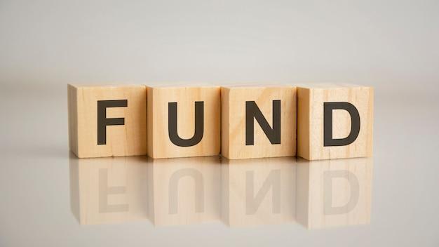 Cztery drewniane kostki z literami funduszu. koncepcja marketingu biznesowego. odbicie napisu na lustrzanej szarej powierzchni stołu