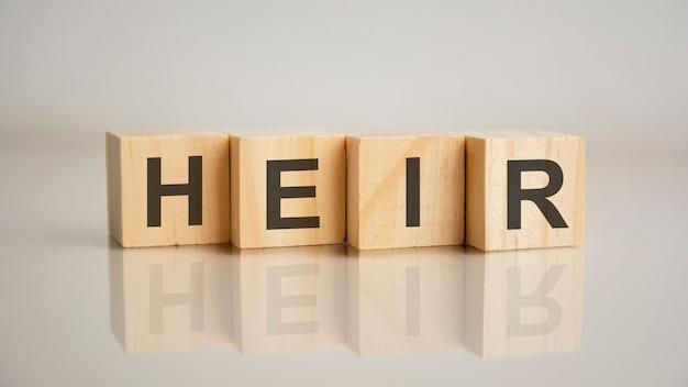 Cztery drewniane kostki z literami spadkobiercy. koncepcja marketingu biznesowego. odbicie napisu na lustrzanej szarej powierzchni stołu
