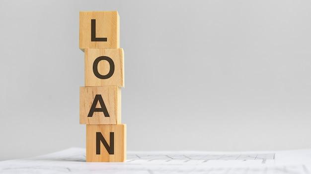 Cztery drewniane kostki z napisem pożyczka na tle białych sprawozdań finansowych, silna koncepcja biznesowa. szare tło