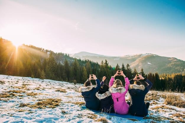 Cztery dziewczyny siedzą w śniegu, plecach do kamery, ręce i tworzą serce w górach zimowych