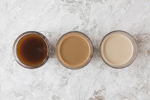 Cztery filiżanki kawy w rzędzie na tle marmuru wyświetlające różne mieszanki mleka i kawy