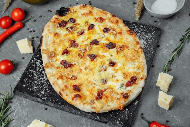 Cztery gorące sery pyszne rustykalna amerykańska pizza z grubą skórką na czarnym stole.