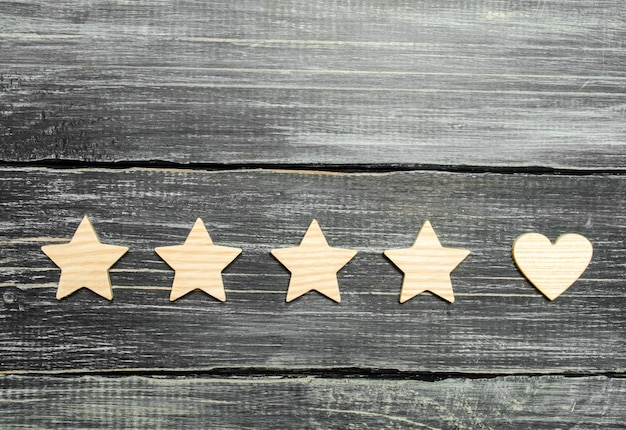 Cztery gwiazdki i serce na ciemnym tle. wybór klientów użytkowników.