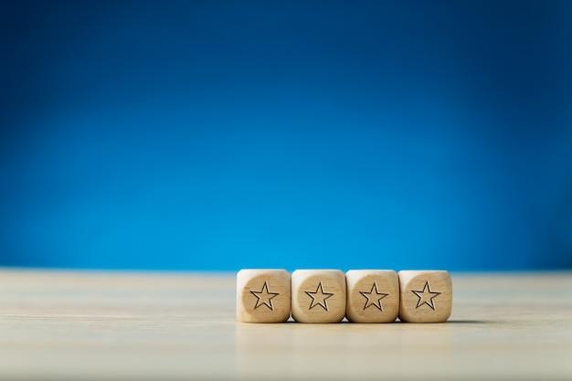 Cztery gwiazdki na czterech drewnianych kostkach ułożone w rzędzie. na niebieskim tle z miejsca na kopię.