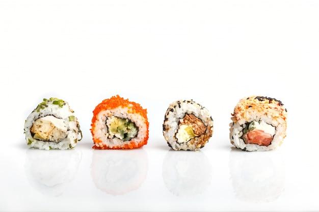 Cztery japońskiej maki suszi rolki z łososiem odizolowywającym na bielu z rzędu