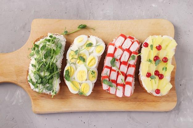 Cztery kanapki na grzance z groszkiem, ananasem, czerwoną porzeczką, paluszkami krabowymi i jajkiem przepiórczym na drewnianej desce