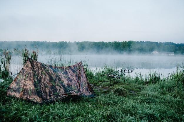 Cztery karpiowe wędki w wędce na powierzchni jeziora w pobliżu namiotu kempingowego