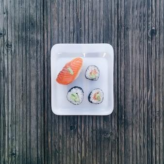 Cztery kawałki sushi na małej tabliczce