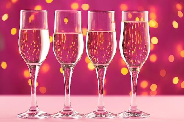 Cztery kieliszki do szampana na różowym tle z niewyraźnymi światłami wianek