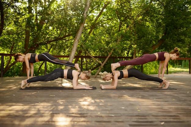 Cztery kobiety robi ćwiczenia równowagi na grupowym treningu jogi w letnim parku