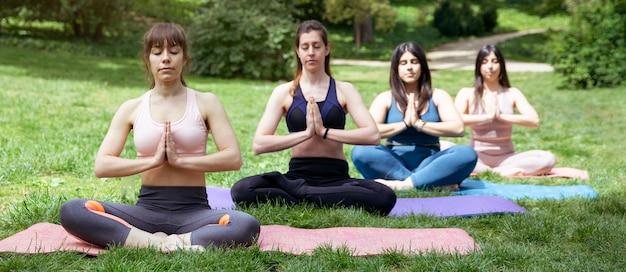 Cztery kobiety robią medytację na zewnątrz. grupowe ćwiczenia jogi w parku.