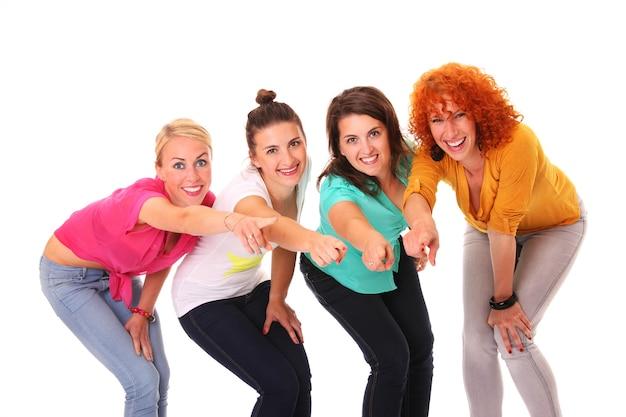 Cztery kobiety uśmiechające się i wskazujące na coś nad białymi
