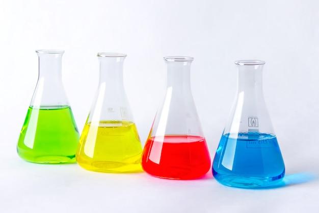 Cztery kolby laboratoryjne z kolorowych płynów na białym.