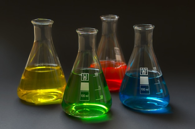 Cztery kolby laboratoryjne z kolorowymi płynami na białym tle na ciemnym tle.