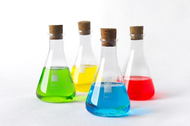 Cztery kolby laboratoryjne z korkiem i kolorowe płyny na białym.